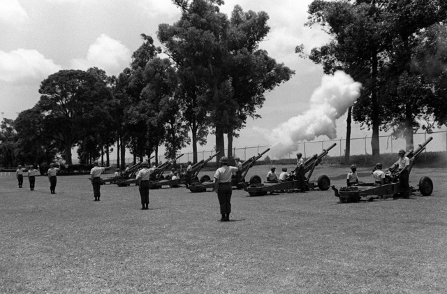 Members of Btry. C, 2nd Bn., 11th Field Arty., 25th Inf. Div., Schofield Barracks, fire 105mm howitzers in a 21-gun salute in honor of the soldiers who died for their country