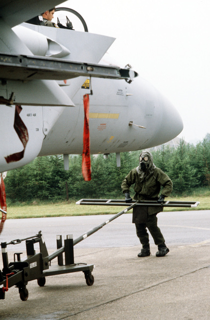 A ground crew member attaches a tow bar to an F-15 Eagle aircraft to roll the aircraft out during chemical warfare training. The aircraft is assigned to the 71st Tactical Fighter Squadron, 1ST Tactical Fighter Wing, involved in exercise SIDEWINDER II