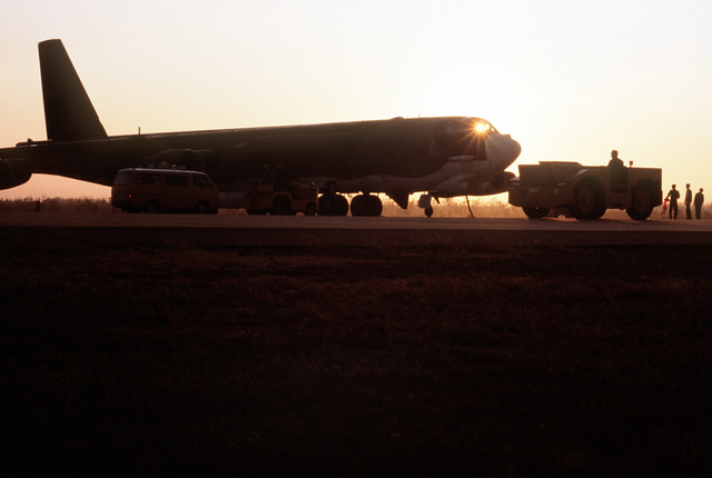 A right front view of a parked B-52H Stratofortress aircraft silhouetted against the sunrise. The aircraft, assigned to the 37th Bomb Squadron, is participating in Exercise Glad Customer '82