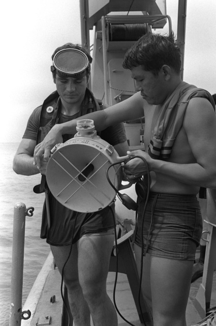 A Royal Thai navy diver assists Hull Maintenance Technician 1ST Class (HT1) Mike Scott with a hand-held sonar as he prepares to enter the water during the mine recovery phase of Exercise Cobra Gold '82