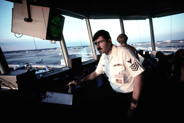 Air Controlman 1ST Class Dave Atkins helps direct air traffic from the control tower of the Miami International Airport. Military personnel were moved into positions vacated by striking members of the Professional Air Traffic Controllers Organization