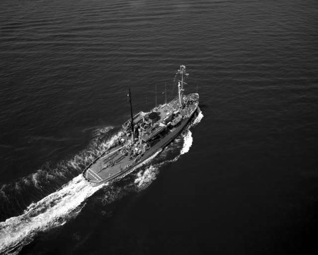 An aerial starboard quarter view of the salvage ship USS RECOVERY (ARS 43) underway