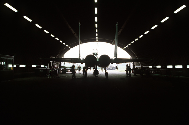 Fish-eye rear view of an F-15A Eagle aircraft silhouetted against a tab-vee shelter's opening. The Eagle, from the 71st Tactical Fighter Squadron, 1ST Tactical Fighter Wing is undergoing chemical warfare maintenance during exercise SIDEWINDER II