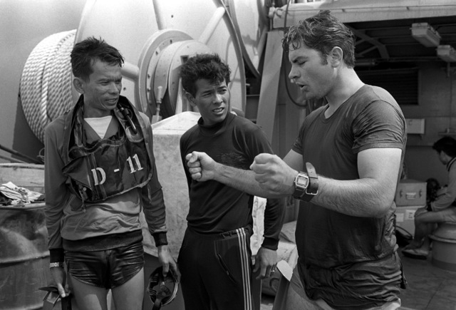 Hull Maintenance Technician 1ST Class (HT1) Mike Scott (right) goes over problems encountered with the hand-held sonar with ENS. Chao (left) and LT J.G. Piroj. Royal Thai navy, during Exercise Cobra Gold '82