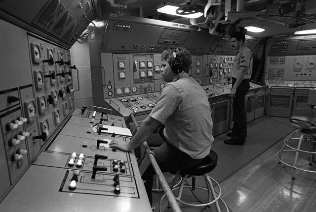 Machinist's Mate 2nd Class Melvin Johnson, standing, monitors the automatic combustion control system in the engineering main control room aboard the fleet oiler USS CIMARRON (AO-177), while an interior communications technician mans the electrical console