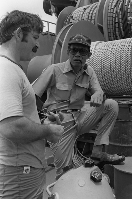Radioman 1ST Class (RM1) Fred Pasteris explains mine search and recovery operations to Royal Thai Navy ADM Payao (right) during Exercise Cobra Gold '82