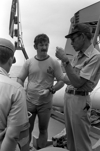 Radioman 1ST Class (RM1) Fred Pasteris (middle) explains mine search and recovery operations to Royal Thai Navy ADM Payao during Exercise Cobra Gold '82