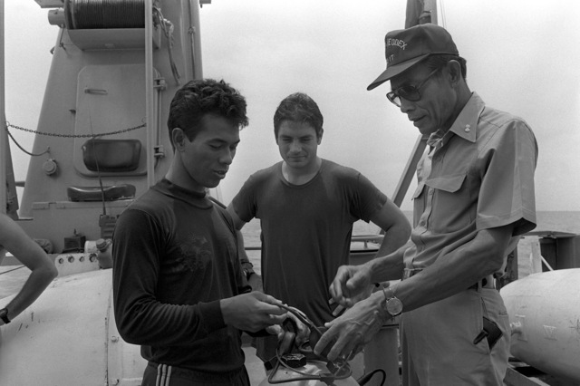 Royal Thai navy diver (RTN) LT J.G. Piroj (left) discusses a hand-held sonar with RTN ADM Payao (right) and Hull Maintenance Technician 1ST Class (HT1) Mike Scott during Exercise Cobra Gold '82