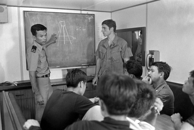 Royal Thai navy ENS Chao (left) translates a training lecture given by Hull Maintenance Technician 1ST Class (HT1) Mike Scott, Explosive Ordnance Disposal Group One, into Thai during Exercise Cobra Gold '82