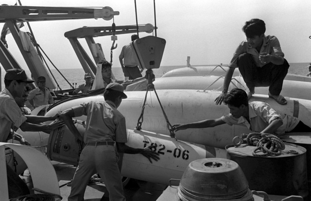 Royal Thai navy personnel transfer recovered mines to the support ship HTMS Thalang during the mine recovery phase of Exercise Cobra Gold '82