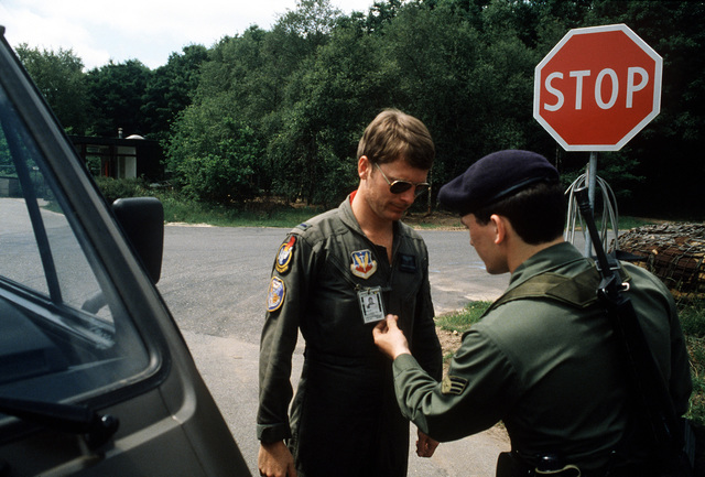 SRA Mike Lynott checks the line badge of 1LT Garth Anderson at a gate during Exercise Sidewinder II. LT Anderson is from the 71st Tactical Fighter Squadron, and AMN Lynott, a security policeman from the 32nd Tactical Fighter Squadron. Both squadrons are assigned to the 1ST Tactical Fighter Wing