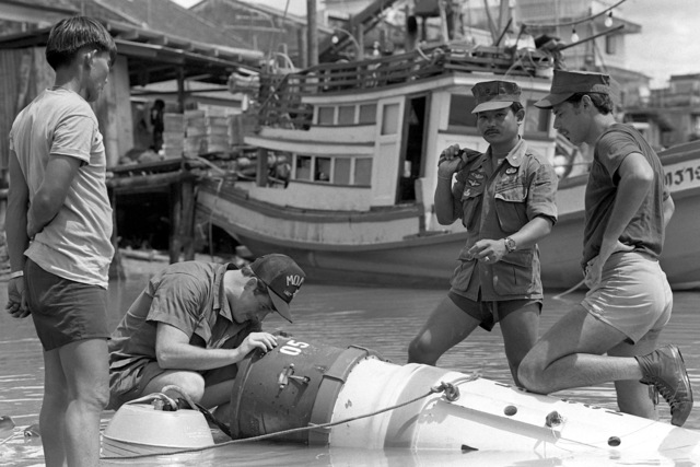 Thai Explosive Ordnance Disposal expert CPO Suvit (center), and U.S. Navy Mineman 2nd Class Mike Hulliger and Hull Maintenance Technician 1ST Class Fred Williams (right) investigate a mine picked up in a fishing net and dragged into shore during Exercise Cobra Gold '82