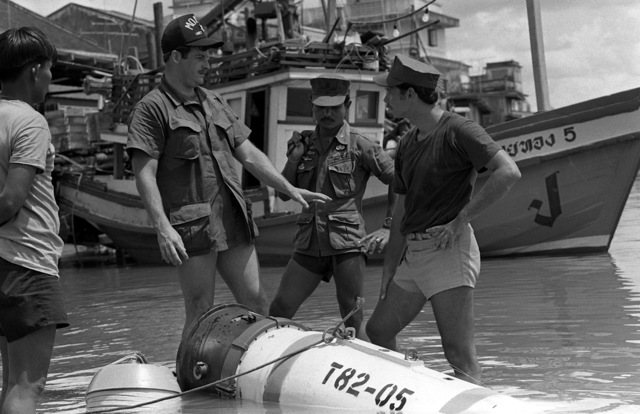 Thai Explosive Ordnance Disposal expert CPO Suvit, (center), and U.S. Navy Mineman 2nd Class Mike Hulliger and Hull Maintenance Technician 1ST Class Fred Williams, (right), investigate a mine picked up in a fishing net and dragged into shore during Exercise Cobra Gold '82