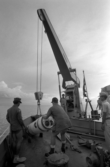 Thai Explosive Ordnance Disposal expert CPO Suvit (left) watches as U.S. Navy Mineman 2nd Class Mike Hulliger guides a mine, as it is lifted by crane aboard the support ship HTMS Thalang during Exercise Cobra Gold '82