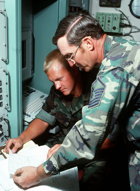 TSGT David Hillman and SMSGT Chuck Blair (left to right), from the senior level technical management, review technical order procedures on the completed Weapons Control System. The Air Force is conducting a test and evaluation program for the ground-launched cruise missile's weapon system at the Integrated Maintenance Facility