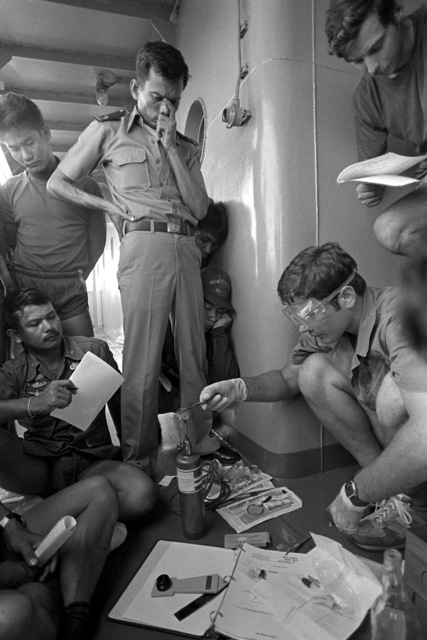 U.S. and Royal Thai navy personnel listen to a training lecture on how to test a fuse. Hull Maintenance Technician 1ST Class (HT1) Mike Scott goes through the procedures as HT1 Fred Williams (standing) reads a check-off list during Exercise Cobra Gold '82