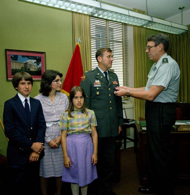 MAJ John G. Zierdt Jr. is presented the Legion of Merit by MGEN Max Noah, director, Program Analysis and Evaluation. Looking on is MAJ Zierdt's wife Gina, daughter, Karen, and son John III