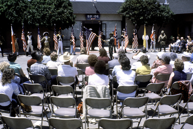 Some residents of the city watch the Marines from the Marine Barracks, Vallejo, California, 12th Marine Corps District, display past U.S. flags and the corresponding Marine uniform for the period that the flag represents. The flag pageant is taking place at the Elks Lodge (BPOE)