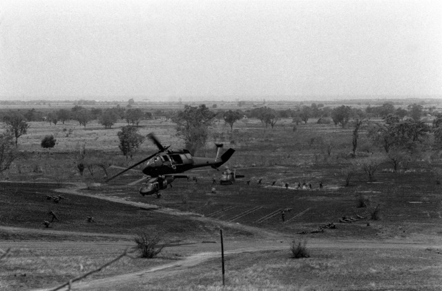 """After dropping off infantrymen in a landing zone, two UH-60A Black Hawk helicopters proceed out of the open area to avoid """"enemy"""" fire, during Exercise Ocean Venture '82"""