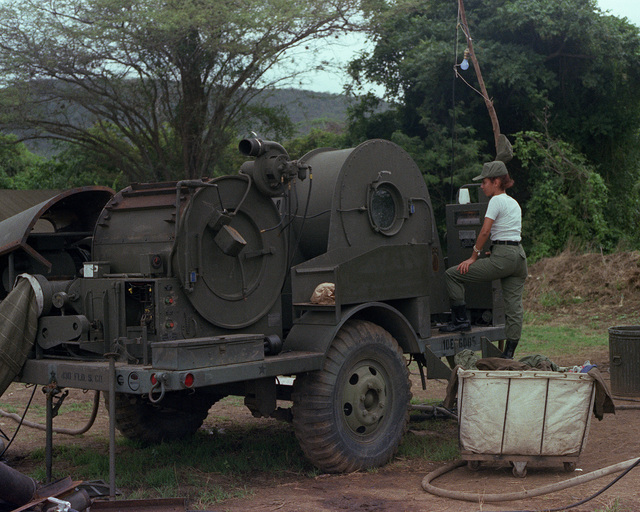An Army reservist from the 430th Field Service Company watches a load of laundry being washed in a mobile laundry unit during Exercise Ocean Venture '82