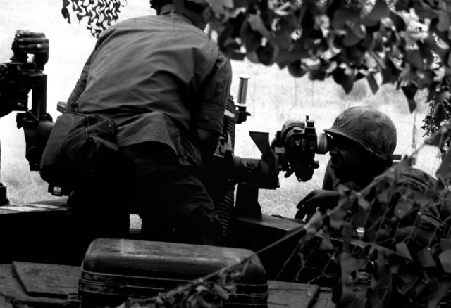 SPC Saupia Olo, left, loads a round of ammunition into 105mm howitzer while SPC Joseph Reynolds sights in on a target during exercise Ocean Venture '82. They are assigned to the 1ST Battalion, 321st Field Artillery