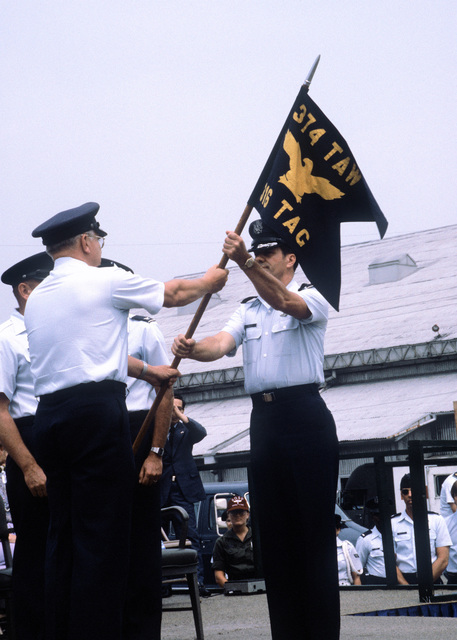 MGEN Donald W. Bennett, commander of the 22nd Air Force, presents command of the 316th Tactical Airlift Group of COL Lowell G. Fathera, who succeeds COL Clark