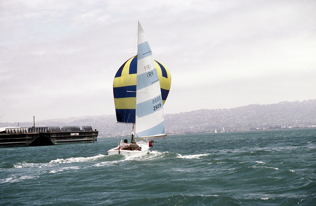 A sail boat, with spinnaker billowing, takes part in the Treasure Island Yacht Club sailing tournament. The Naval Air Station, Lemoore, California sailing team is a participant in the race. A Navy open lighter (YC-980) is in the background