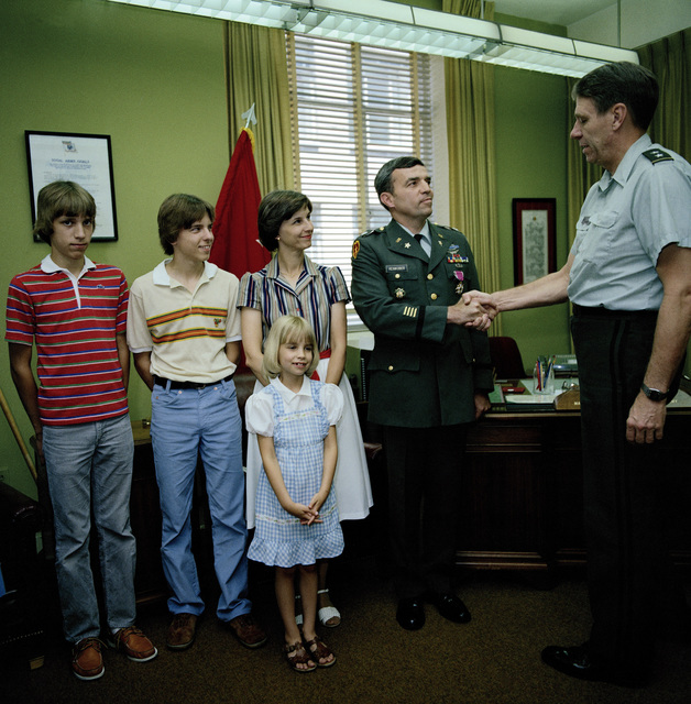 LCOL Thomas E. Reinkober is presented the Legion of Merit by MGEN Max Noah, director, Program Analysis and Evaluation. Looking on is Reinkober's family, from left to right, sons Eric and Brian, wife Pam and Daughter Amy