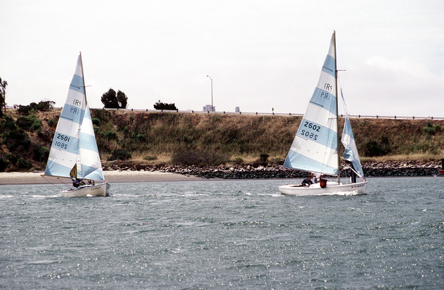 Two sail boats take part in the Treasure Island Yacht Club sailing tournament. The Naval Air Station, Lemoore, California sailing team is a participant in the race