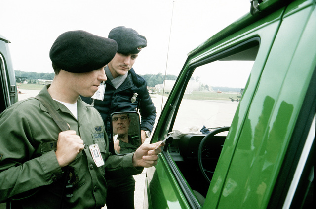 A1C Calvin W. Padgett from the 10th Security Police Squadron, and SSGT Joseph Kraus Jr. from the 363rd Security Police Squadron, check flight line passes at the entry point during Exercise Salty Bee