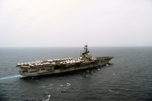 An aerial starboard quarter view of the aircraft carrier USS FORRESTAL (CV-59) underway