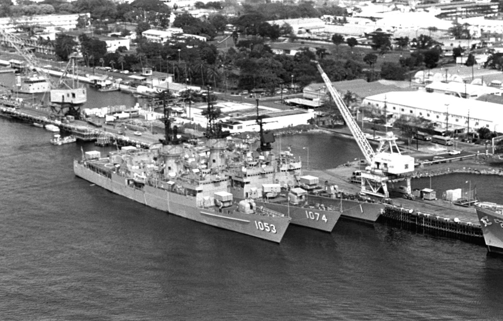 An aerial view of the US Naval Ship Repair Facility. Berthed at the shipyard are the Knox-class frigate USS ROARK (FF 1053) AND USS HAROLD E. HOLT (FF 1074). Moored alongside them is the guided missile frigate USS BROOKE (FFG 1)