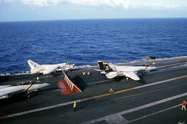 An F-14 Tomcat aircraft waits behind the blast deflector panels as another F-14 from Fighter Squadron 84 (VF-84) prepares for launching during flight operations aboard the nuclear-powered aircraft carrier USS CARL VINSON (CVN-70). An A-7E Corsair II aircraft from Light Attack Squadron 82 (VA-82) is ready for launch on the port catapult