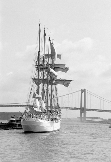 A starboard quarter view of the Chilean training ship ESMERALDA under full sail with the Walt Whitman Bridge in the background. The ship is participating in the Century IV celebration