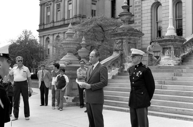 COL Jack R. Lousma, commander, third test mission of the space shuttle Columbia, talks to a group of Marines and poolees in front of the State Capitol building, during the poolees' promotion ceremony. Standing to his left is Marine CPT Robert Steffenson