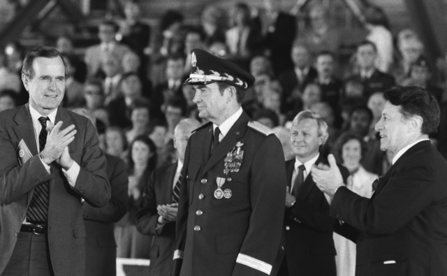 Vice President George Bush (left), Secretary of Defense Caspar Weinberger (right) and the honored guests, stand and clap during the retirement ceremony for GEN David C. Jones, chairman, Joint Chiefs of STAFF (center)