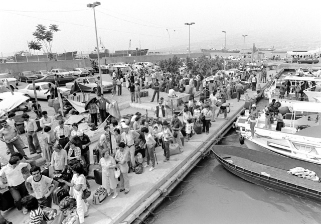 Aerial view of the evacuees waiting on the pier. Utility landing craft (LCUs) are being used to transfer them to waiting U.S. Navy amphibious ships. Approximately 600 Americans and third nation personnel are being evacuated from Beirut