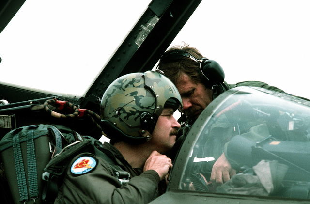A pilot from the 183rd Tactical Fighter Group is assisted by a ground crew member, prior to a training flight aboard an F-4D Phantom II aircraft during Exercise Coronet Brave