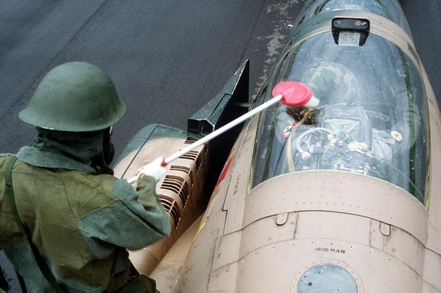 A British Royal Air Force member decontaminates an F-C Phantom II aircraft during chemical warfare training, part of Exercise Coronet Cactus