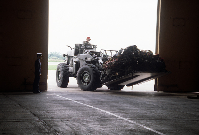 A pallet of United States Air Force luggage is being carried on a forklift into a hangar. The luggage arrives for Exercise Coronet Cactus