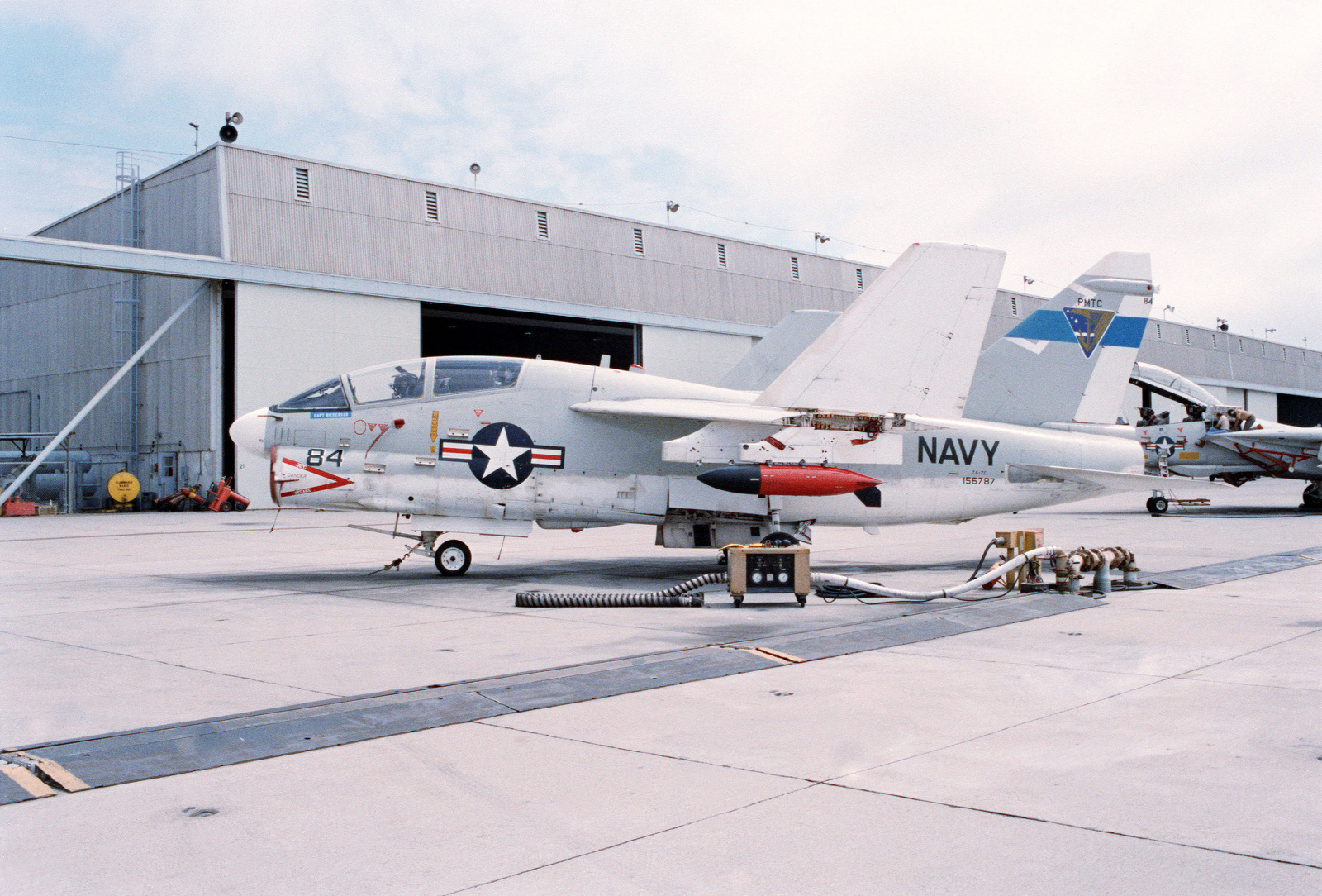 A view of an A-7 Corsair II aircraft fitted with a Radar Simulating Set (RSS)-(JEEP) pod, parked in front of Building 351 at the Pacific Missile Test Center
