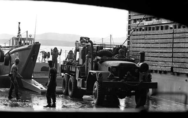 An M-35 cargo truck is backed on to a mechanized landing craft (LCM) from the dock landing ship USS PORTLAND (LSD-37) in preparation for a landing on the island of Vieques, Puerto Rico. The men and equipment are a part of Operation Unitas XXIII