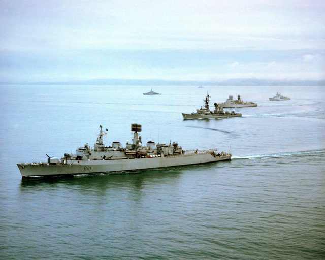 An aerial port view of ships from the Standing Naval Force, Atlantic, underway in formation. The ships are, from foreground to back, the British light cruiser HMS NORFOLK (D-21), the guided missile destroyer USS CLAUDE V. RICKETTS (DDG-5), the Netherlands destroyer HNLMS DERUYTER (F-806), the Canadian frigate HMCS SAQUENAY (206) and the Federal Republic of Germany frigate FGS BRAUNSCHWEIG (F-225)