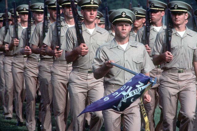 An Aviation Officer Candidate guidon bearer dips the flag as his class passes in review during the graduation ceremony for another class. Candidates must undergo 14 weeks of training before being commissioned as officers