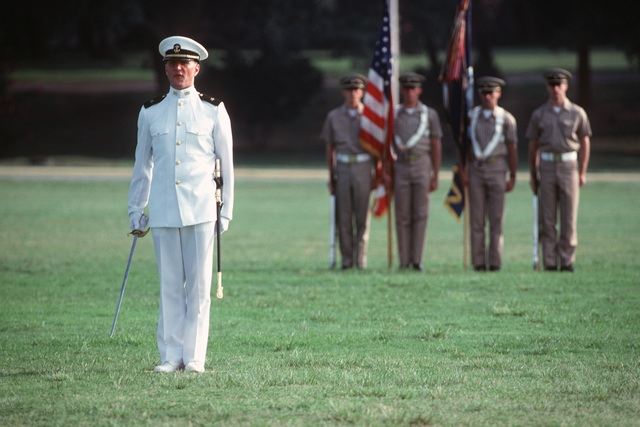 Aviation Officer Candidate, his sword drawn, issues a command during his class's graduation ceremony after 14 weeks of training. A candidate color guard stands behind him