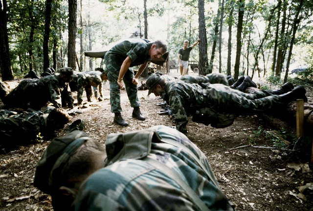 Combat Control School students are doing tough push-ups under the supervision of TSGT Bob Wilkinson. The students are participating in routine daily physical training before becoming Red Berets upon their graduation