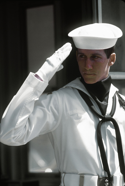 SEAMAN Bill Reed, a member of the Navy Ceremonial Guard, salutes visitors, workers and residents as they enter the gate of the Navy yard