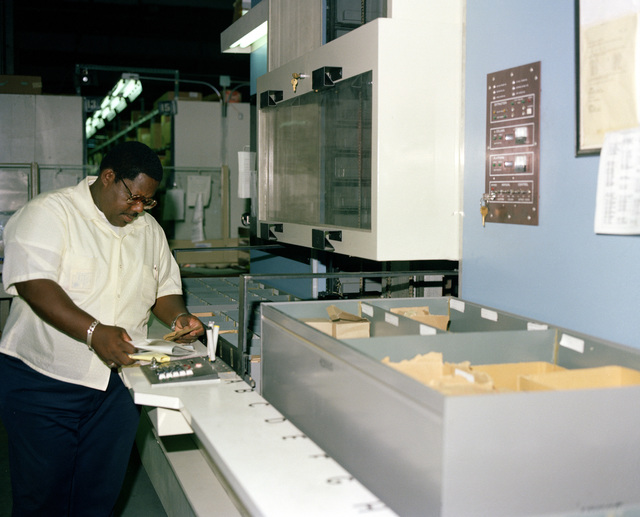 A worker studies an order for parts at the 6505th Supply Squadron storage retriever