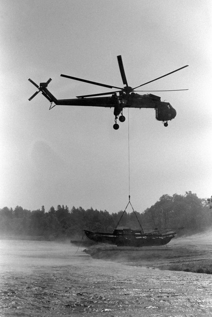 A ground-to-air right side view of a CH-54A Tarhe (Skycrane) helicopter airlifting bridge building equipment to Lake Stillwell for a training exercise of the 724th Combat Engineer Battalion
