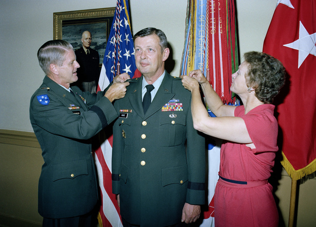 LGEN William R. Richardson, deputy chief of staff for Operations and Plans, pins the second star on MGEN James E. Moore Jr. at his promotion ceremony at the Pentagon. Assisting with the pinning is Mrs. Moore
